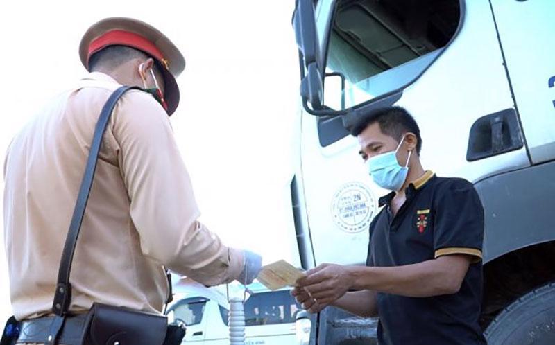 CSGT kiểm tra giấy tờ xe và giấy xét nghiệm Covid-19 của tài xế. Nguồn ảnh: Cục CSGT.